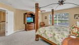 Master bedroom with cabinet mounted LCD cable TV & DVD player with this Orlando Villa for rent direct from owner