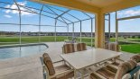 View from covered lanai towards pool and golf course beyond with this Orlando Villa for rent direct from owner