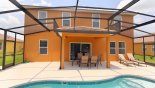 View of pool towards covered shady lanai with patio table & 6 chairs from Calabria rental Villa direct from owner