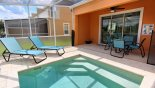 Pool deck with 2 sun loungers and shady lanai from Eliora 5 Townhouse for rent in Orlando