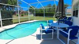 View of pool deck with 2 patio tables, 8 chairs and a parasol - www.iwantavilla.com is the best in Orlando vacation Villa rentals