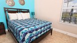 bedroom 5 with queen sized bed & views onto pool deck from Castillo 2 Villa for rent in Orlando