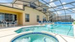View of pool & spa towards covered lanai with patio table & 4 chairs - www.iwantavilla.com is the best in Orlando vacation Villa rentals