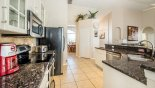 Kitchen viewed towards dining area through arched opening with this Orlando Villa for rent direct from owner
