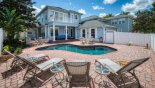 View of pool deck from behind the 4 sun loungers - www.iwantavilla.com is the best in Orlando vacation Villa rentals