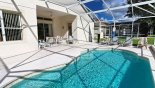 View of pool towards covered lanai showing 2 reclining chairs with foot stools from Jasmine 9 Villa for rent in Orlando
