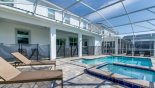 Spacious rental Champions Gate Villa in Orlando complete with stunning Pool & spa viewed towards covered lanai showing 4 sun loungers