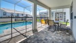 Seating for 6 people under covered lanai area on pool deck with this Orlando Villa for rent direct from owner