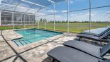 4 comfortable sun loungers overlooking covered pool - www.iwantavilla.com is the best in Orlando vacation Villa rentals