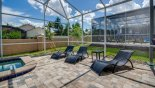 Three  comfortable sun loungers and table at top of pool deck with this Orlando Villa for rent direct from owner