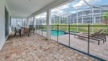 Covered lanai showing pool safety fence erected with this Orlando Villa for rent direct from owner