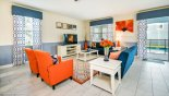 Villa rentals in Orlando, check out the Colorful family room with seating around large LCD cable TV