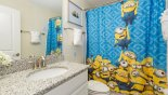 Spacious rental Champions Gate Villa in Orlando complete with stunning Family bathroom #4 with Minions theming - bath with shower over