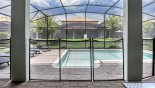 View onto pool from covered lanai showing pool safety fence erected with this Orlando Villa for rent direct from owner