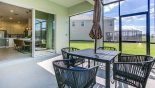 Spacious rental Solterra Resort Villa in Orlando complete with stunning Patio table viewed towards covered lanai & sliding doors leading to dining area
