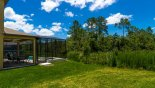 Villa rentals in Orlando, check out the View of pool deck from outside the pool cage showing lush conservation area