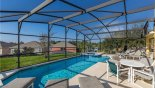 The expansive pool and deck with one of two outdoor tables and sets of 4 chairs with this Orlando Villa for rent direct from owner