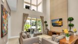 Living room with cathedral ceiling viewed towards covered lanai & private balcony above from Delight 4 Townhouse for rent in Orlando