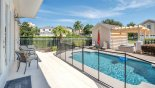 View of sunny pool deck towards garage with this Orlando Villa for rent direct from owner