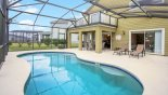 Spacious rental Providence Villa in Orlando complete with stunning Pool deck viewed towards covered lanai with private balcony above